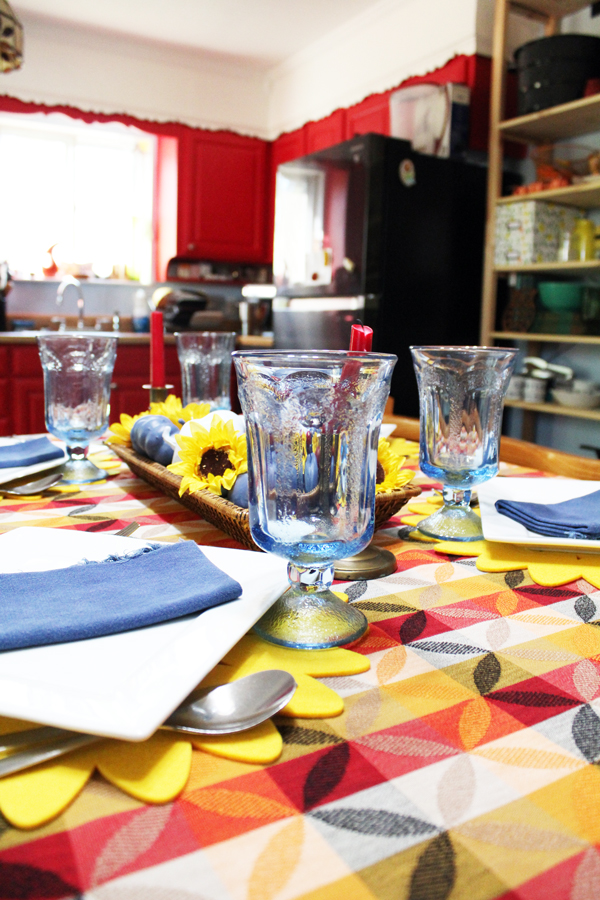 red, blue and yellow tablescape with red kitchen cabinets in the background
