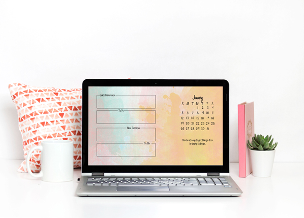 Laptop with the January background. It sits on a white surface with a pink pillow, a coffee mug, a book, and a succulent in a white planter.