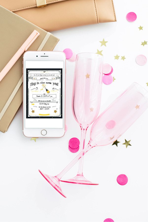 two empty pink champagne glasses laying on their sides by a smartphone with a party invitation on the screen