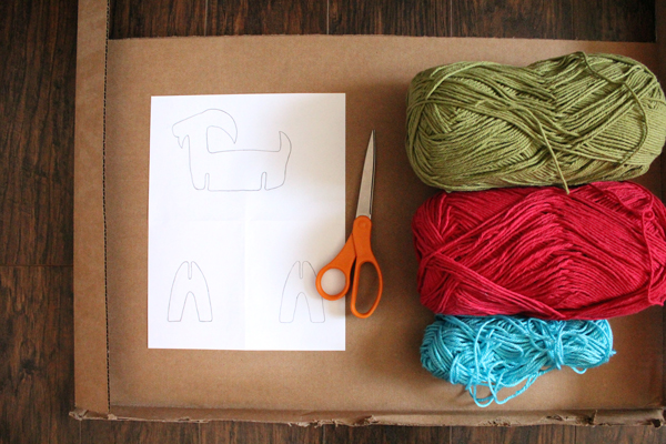 green, red, and blue yarn sitting beside a paper template an a pair of scissors on top of a large piece of cardboard