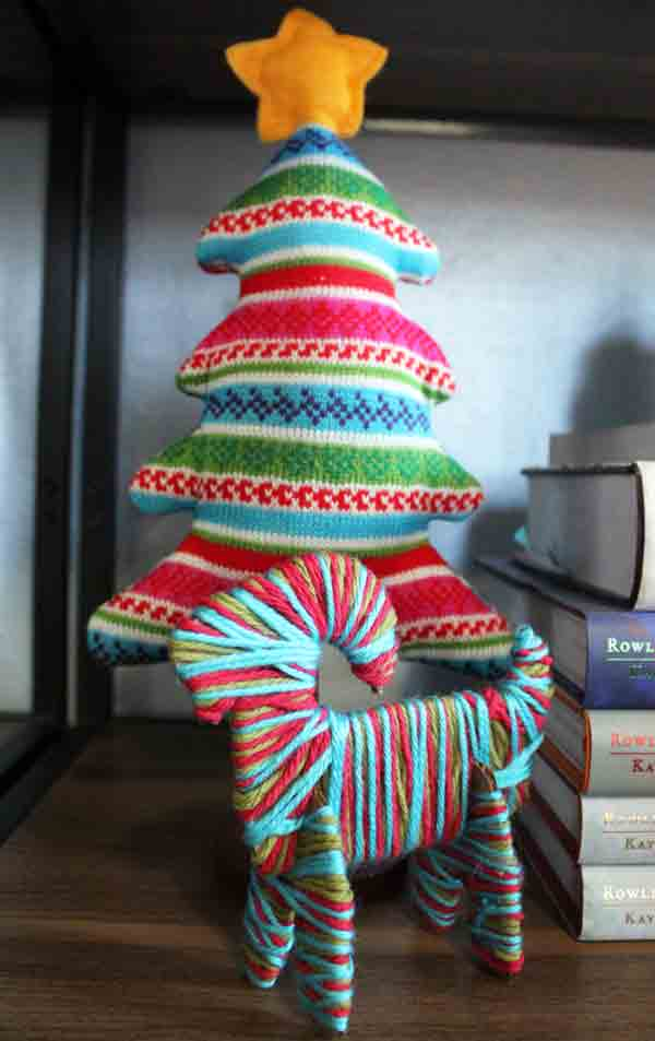 the yarn goat stands in front of a fabric tree in matching colors