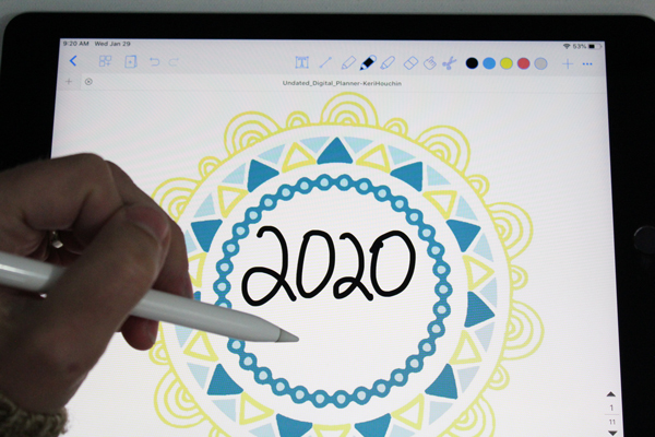 """hand using an apple pencil to write """"2020"""" in the center of a mandala"""