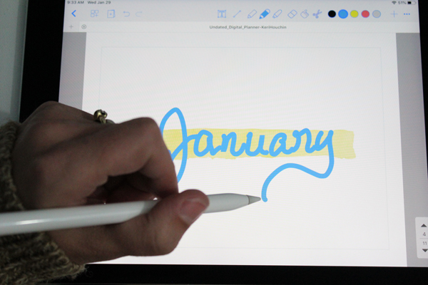 """a left hand holding an apple pencil and writing """"January"""" on an ipad screen"""