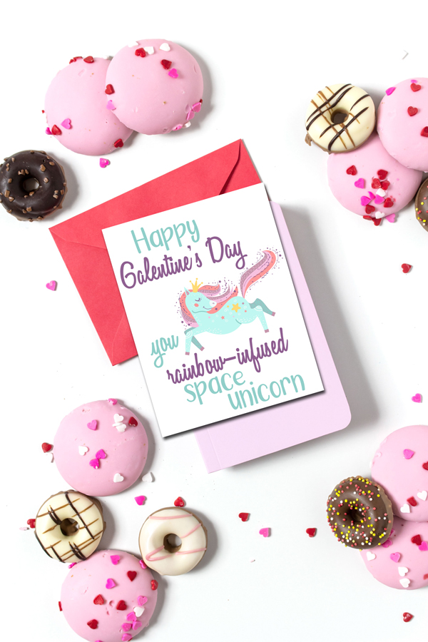 """white table full of doughnuts with a card in the center with a unicorn and the text """"Happy Galentine's Day you rainbow-infused space unicorn"""""""